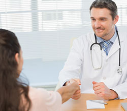 smiling-male-doctor-and-patient-shaking-hands-in-the-medical-office